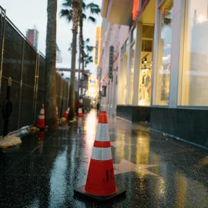 JBC Safety Plastic Revolution Series Orange Traffic Cone with Reflective Collar on Sidewalk